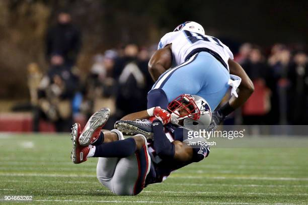 Patrick Chung of the New England Patriots tackles Jonnu Smith of the Tennessee Titans during the second quarter in the AFC Divisional Playoff game...