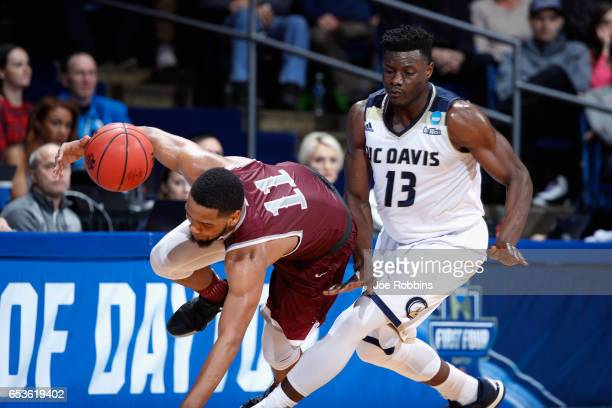 Patrick Cole of the North Carolina Central Eagles falls against JT Adenrele of the UC Davis Aggies in the second half during the First Four game in...