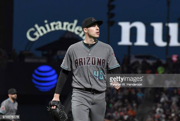 Patrick Corbin of the Arizona Diamondbacks walks back to the dugout after striking out three batters in a row with the bases loaded against the San...