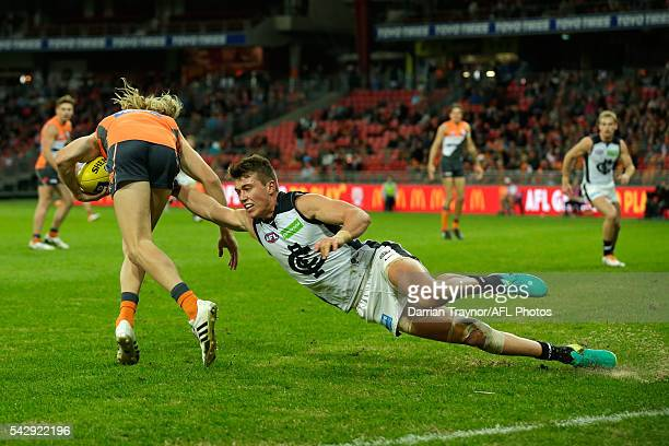 Patrick Cripps of the Blues dives in an attempt to tackle Nick Haynes of the Giants during the round 14 AFL match between the Greater Western Sydney...