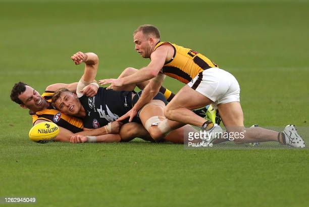 Patrick Cripps of the Blues gets tackled by Jonathon Ceglar and Tom Mitchell of the Hawks during the round nine AFL match between the Carlton Blues...