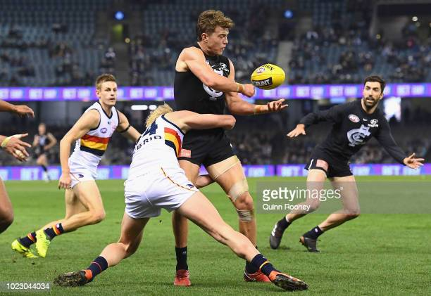 Patrick Cripps of the Blues handballs whilst being tackled by Elliott Himmelberg of the Crows during the round 23 AFL match between the Carlton Blues...