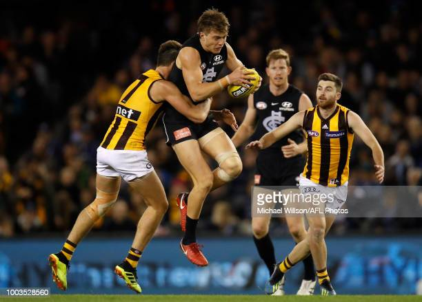 Patrick Cripps of the Blues is tackled by Daniel Howe of the Hawks during the 2018 AFL round 18 match between the Carlton Blues and the Hawthorn...