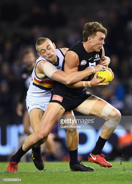 Patrick Cripps of the Blues is tackled by Hugh Greenwood of the Crows during the round 23 AFL match between the Carlton Blues and the Adelaide Crows...