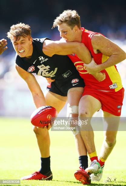 Patrick Cripps of the Blues is tackled by Ryan Davis of the Suns during the round two AFL match between the Carlton Blues and the Gold Coast Suns at...