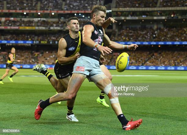 Patrick Cripps of the Blues kicks whilst being tackled by Jack Graham of the Tigers during the round one AFL match between the Richmond Tigers and...