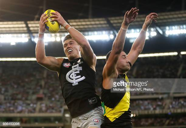 Patrick Cripps of the Blues marks the ball over Shaun Grigg of the Tigers during the 2018 AFL round 01 match between the Richmond Tigers and the...