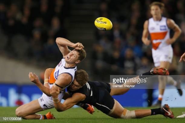 Patrick Cripps of the Blues tackles Jacob Hopper of the Giants during the round 20 AFL match between the Carlton Blues and the Greater Western Sydney...