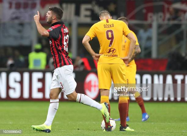 Patrick Cutrone of AC Milan celebrates the winning goal as Edin Dzeko looks dejected during the serie A match between AC Milan and AS Roma at Stadio...