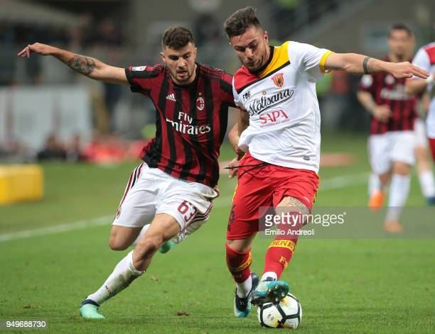 Patrick Cutrone of AC Milan competes for the ball with AlinDorinel Tosca of Benevento Calcio during the serie A match between AC Milan and Benevento...