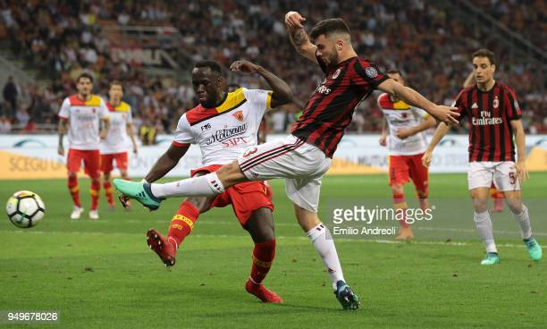 Patrick Cutrone of AC Milan is challenged by Bacary Sagna of Benevento Calcio during the serie A match between AC Milan and Benevento Calcio at...