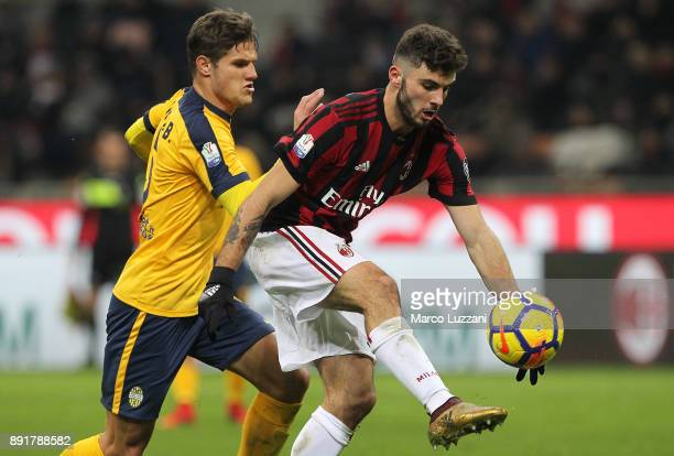 Patrick Cutrone of AC Milan is challenged by Bruno Zuculini of Hellas Verona FC during the Tim Cup match between AC Milan and Hellas Verona FC at...