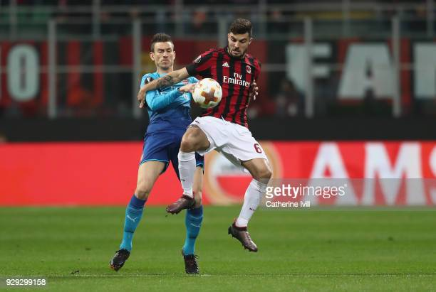 Patrick Cutrone of AC Milan is challenged by Laurent Koscielny of Arsenal during the UEFA Europa League Round of 16 match between AC Milan and...
