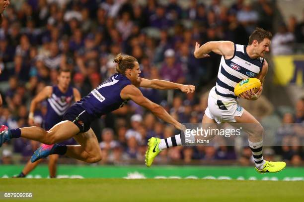 Patrick Dangerfield of the Cats breaks clear of a tackle by Nathan Fyfe of the Dockers during the round one AFL match between the Fremantle Dockers...