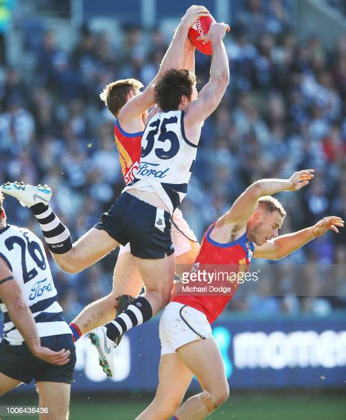 Patrick Dangerfield of the Cats competes for the ball against Josh Walker of the Lions during the round 19 AFL match between the Geelong Cats and the...