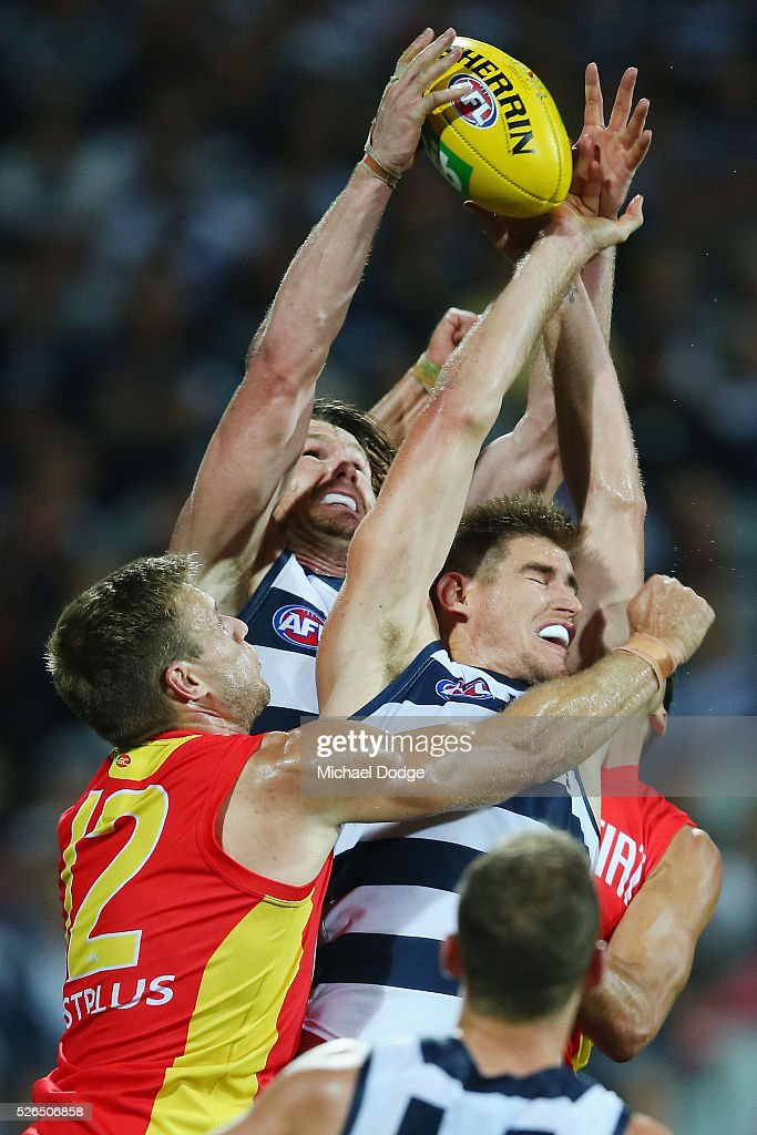 Patrick Dangerfield (L) of the Cats competes for the ball with teammate Tom Lonergan of the Cats and against Sam Day of the Suns during the round six AFL match between the Geelong Cats and the Gold Coast Suns at Simonds Stadium on April 30, 2016 in Geelong, Australia.