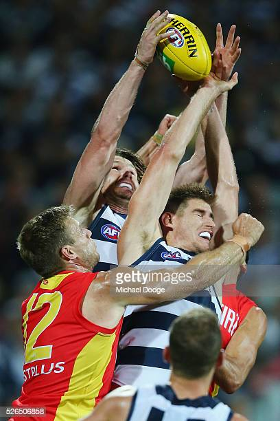 Patrick Dangerfield of the Cats competes for the ball with teammate Tom Lonergan of the Cats and against Sam Day of the Suns during the round six AFL...