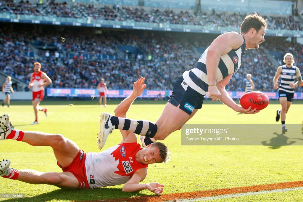 Patrick Dangerfield of the Cats handballs as he break the tackle of Kieren Jack of the Swans during the round six AFL match between the Geelong Cats and Sydney Swans at GMHBA Stadium on April 28, 2018 in Geelong, Australia.