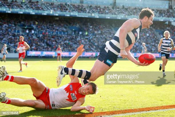Patrick Dangerfield of the Cats handballs as he break the tackle of Kieren Jack of the Swans during the round six AFL match between the Geelong Cats...