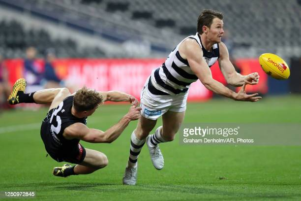 Patrick Dangerfield of the Cats handballs as he is tackled during the round 3 AFL match between the Geelong Cats and the Carlton Blues at GMHBA...