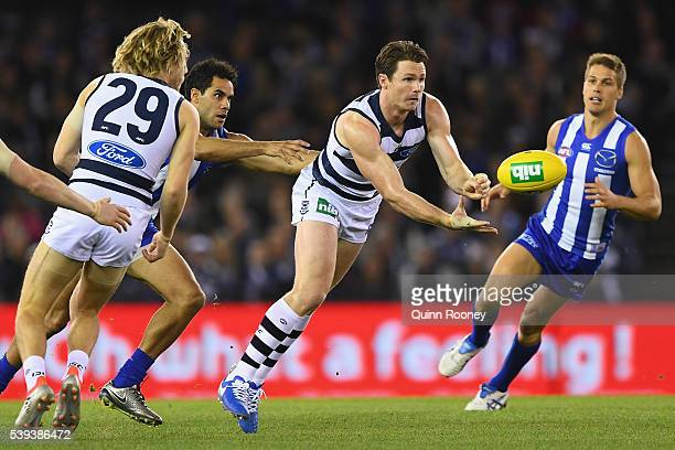 Patrick Dangerfield of the Cats handballs during the round 12 AFL match between the Geelong Cats and the North Melbourne Kangaroos at Etihad Stadium...