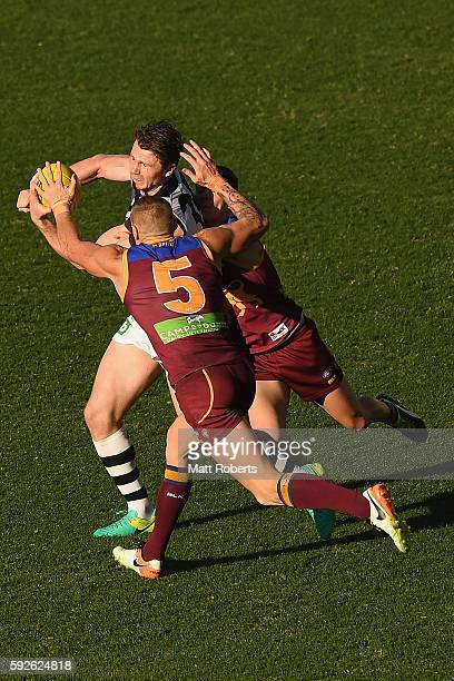 Patrick Dangerfield of the Cats handballs under pressure during the round 22 AFL match between the Brisbane Lions and the Geelong Cats at The Gabba...