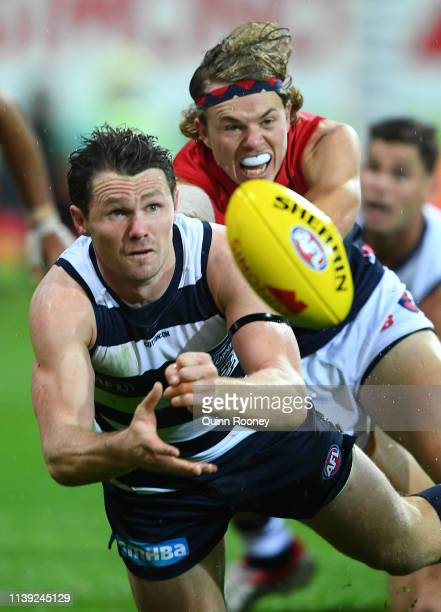 Patrick Dangerfield of the Cats handballs whilst being tackled by Jayden Hunt of the Demons during the round two AFL match between the Geelong Cats...