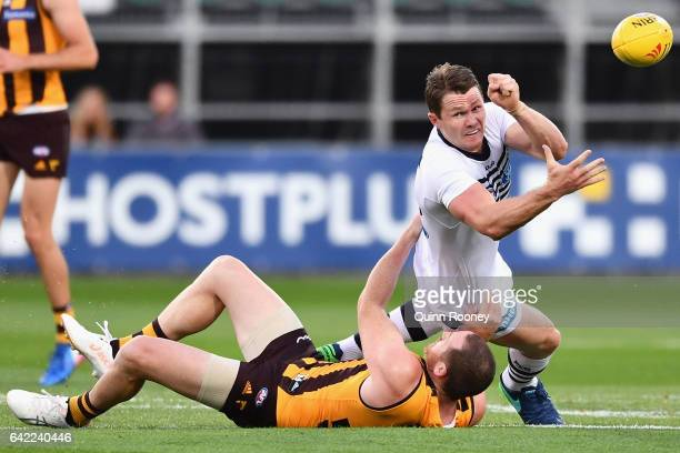 Patrick Dangerfield of the Cats handballs whilst being tackled by Jarryd Roughead of the Hawks during the 2017 JLT Community Series match between the...