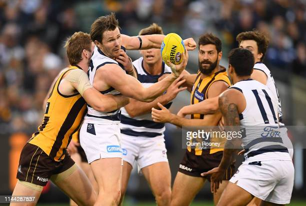 Patrick Dangerfield of the Cats handballs whilst being tackled during the round 5 AFL match between Hawthorn and Geelong at Melbourne Cricket Ground...