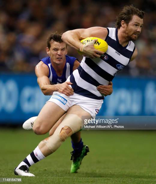 Patrick Dangerfield of the Cats is tackled by Kayne Turner of the Kangaroos during the 2019 AFL round 08 match between the North Melbourne Kangaroos...