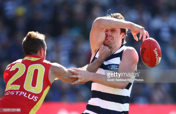 Patrick Dangerfield of the Cats is tackled by Michael Barlow of the Suns during the round 23 AFL match between the Geelong Cats and the Gold Coast...