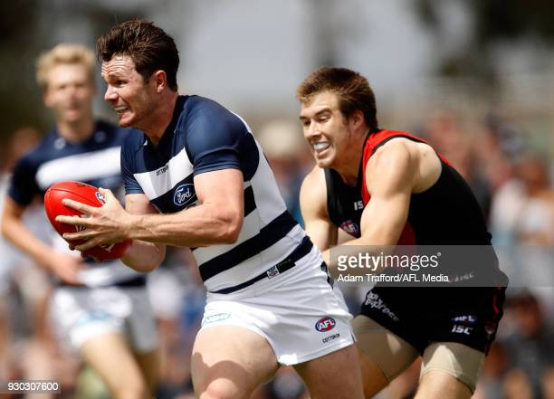 Patrick Dangerfield of the Cats is tackled by Zach Merrett of the Bombers during the AFL 2018 JLT Community Series match between the Geelong Cats and...