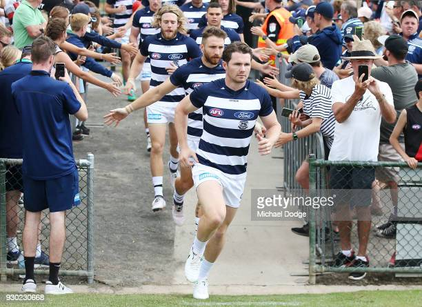 Patrick Dangerfield of the Cats leads the team out during the JLT Community Series AFL match between the Geelong Cats and the Essendon Bombers at...