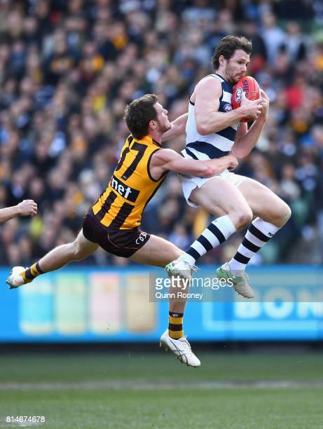 Patrick Dangerfield of the Cats marks over the top of Blake Hardwick of the Hawks during the round 17 AFL match between the Geelong Cats and the...