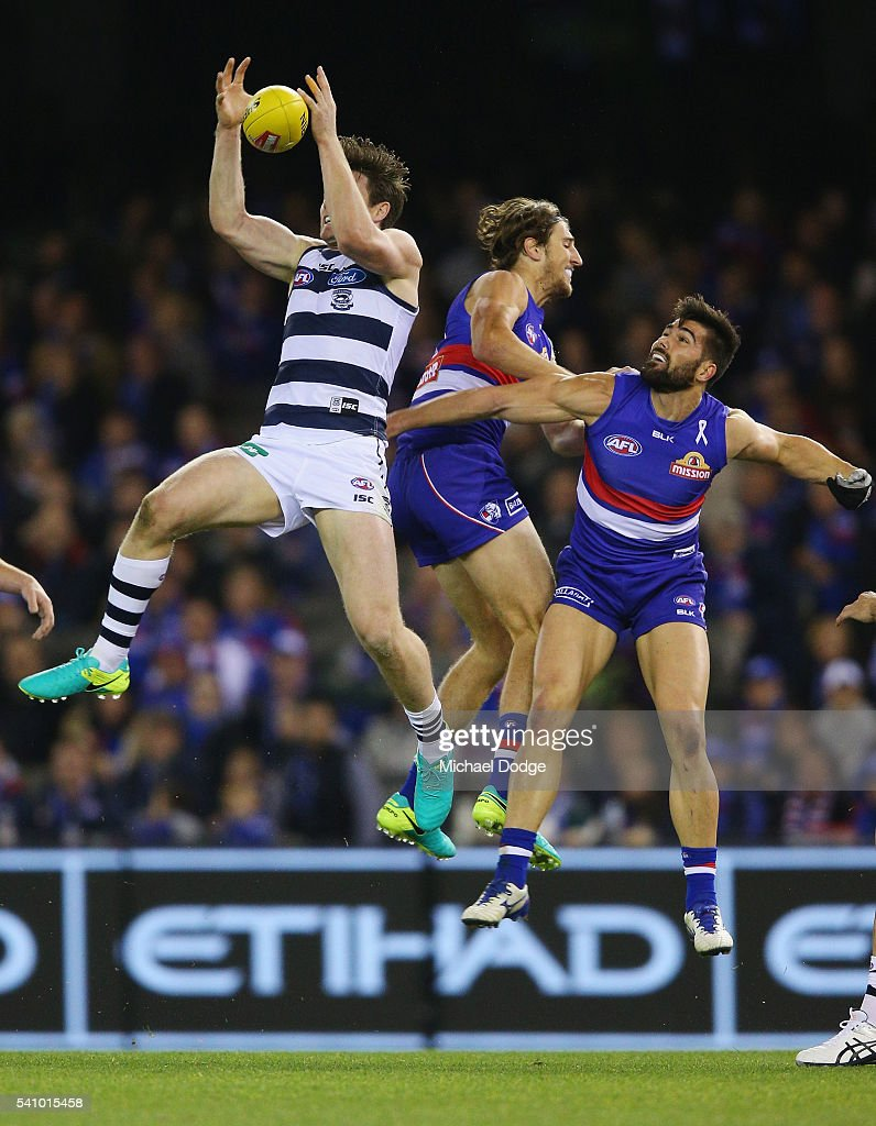 Patrick Dangerfield of the Cats marks the ball against Marcus Bontempelli (C) and Marcus Adams during the round 13 AFL match between the Western Bulldogs and the Geelong Cats at Etihad Stadium on June 18, 2016 in Melbourne, Australia.
