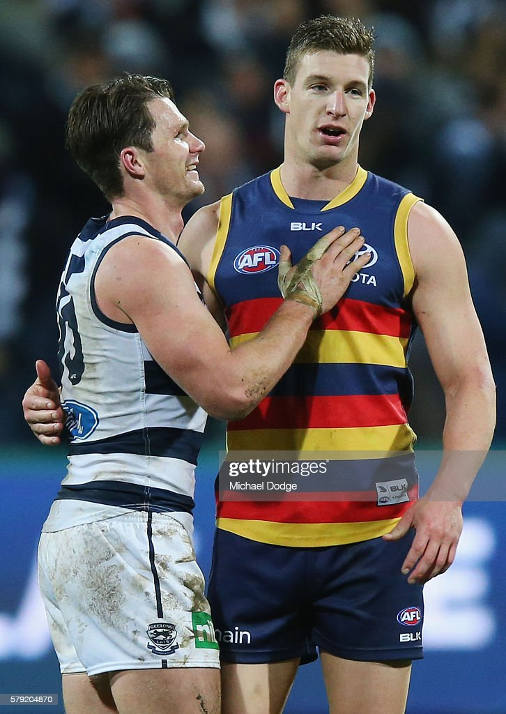 Patrick Dangerfield (L) of the Cats pats good matJosh Jenkins of the Crows after his win during the round 18 AFL match between the Geelong Cats and the Adelaide Crows at Simonds Stadium on July 23, 2016 in Geelong, Australia.