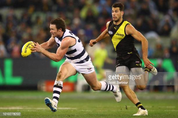 Patrick Dangerfield of the Cats runs with the ball as Alex Rance of the Tigers defends during the round 20 AFL match between the Richmond Tigers and...
