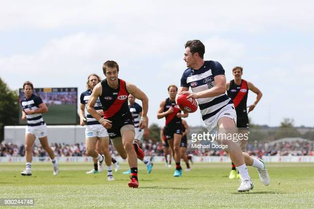 Patrick Dangerfield of the Cats runs with the ball from Zach Merrett of the Bombers during the JLT Community Series AFL match between the Geelong...