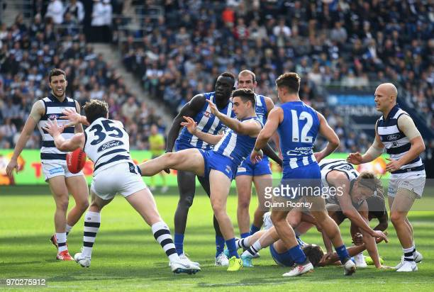 Patrick Dangerfield of the Cats smouthers a kick by Paul Ahern of the Kangaroos during the round 12 AFL match between the Geelong Cats and the North...