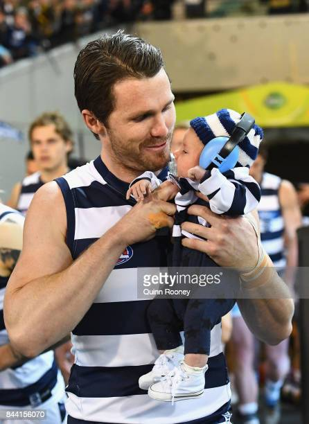 Patrick Dangerfield of the Cats walk out onto the field with his child in his 200th game during the AFL Second Qualifying Final Match between the...