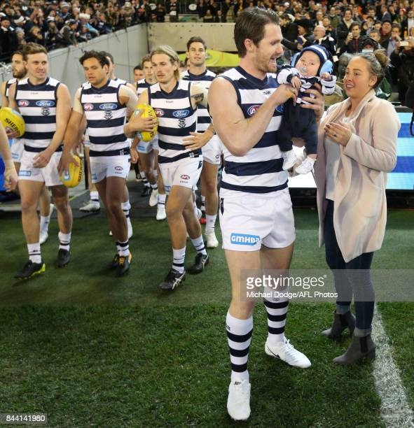 Patrick Dangerfield of the Cats walks out with baby George in front of his wife Mardi for his 200th match during the AFL Second Qualifying Final...