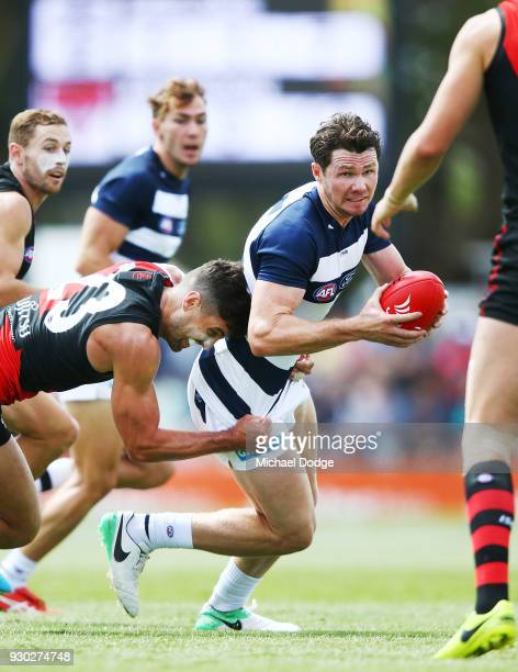 Patrick Dangerfield of the Cats withstands a tackle from David Myers of the Bombers during the JLT Community Series AFL match between the Geelong...