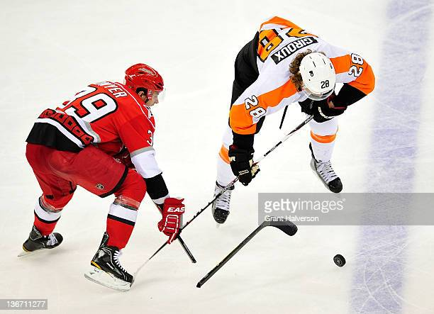 Patrick Dwyer of the Carolina Hurricanes breaks his stick as he challenges Claude Giroux of the Philadelphia Flyers during play at the RBC Center on...