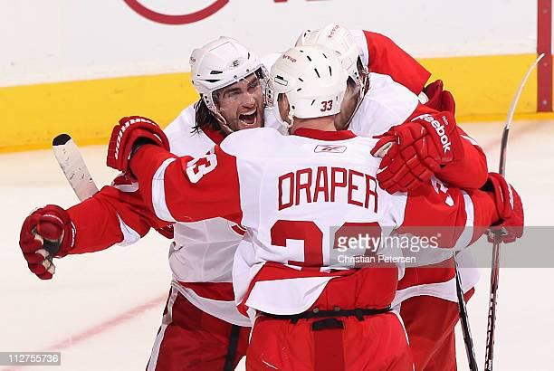 Patrick Eaves of the Detroit Red Wings celebrates with teammates Kris Draper and Darren Helm after scoring a first period goal against the Phoenix...