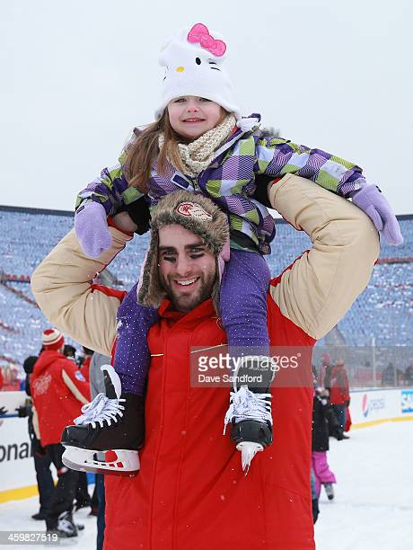 Patrick Eaves of the Detroit Red Wings skates with his daughter Norah after the 2014 Bridgestone NHL Winter Classic team practice session on December...