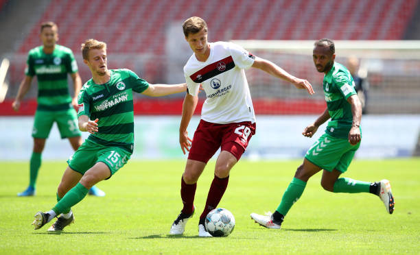 Patrick Erras of 1 FC Nuernberg is challenged by Sebastian Ernst and Julian Green of SpVgg Greuther Fuerth during the Second Bundesliga match between...