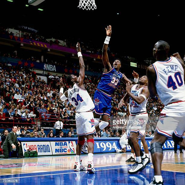 84cba653a Patrick Ewing of the Eastern Conference All Stars shoots a jumper against  Hakeem Olajuwon of the
