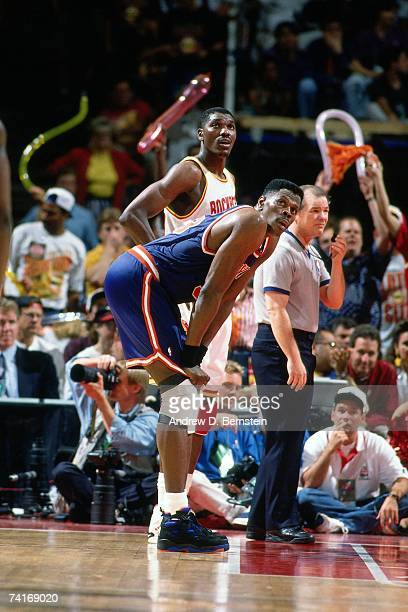 Patrick Ewing of the New York Knicks and Hakeem Olajuwon of the Houston Rockets look up at the scoreboard during Game One of the NBA Finals played on...