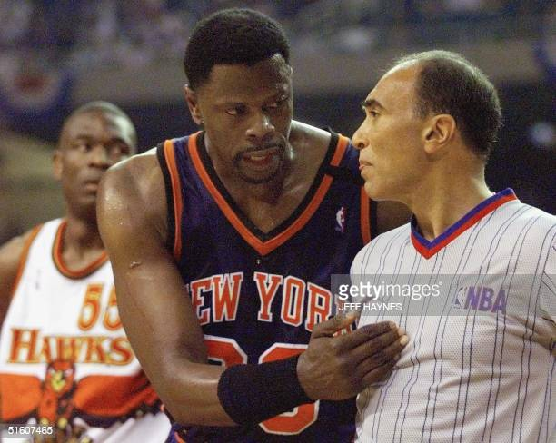 Patrick Ewing of the New York Knicks argues with NBA offical Ronnie Nunn as Dikenbe Mutombo of the Atlanta Hawks looks on 20 May during the first...