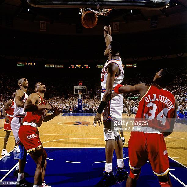 Patrick Ewing of the New York Knicks dunks against Hakeem Olajuwon of the Houston Rockets during Game Four of the NBA Finals played on June 15 1994...